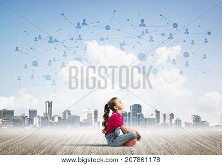Cute kid girl sitting on wooden floor and looking up