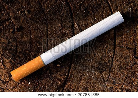 cigarette on a wooden background, a pack of cigarettes, a close-up of a cigarette