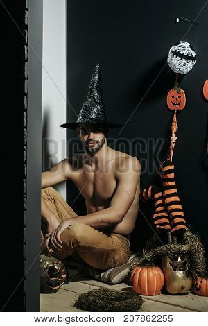 Halloween Macho In Witch Hat And Bared Torso Sitting