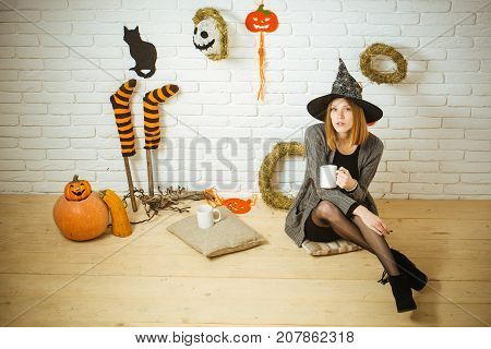 Halloween coffee or tea break. Woman in witch hat with cups. Girl sitting on wooden floor. Holiday celebration concept. Pumpkins stockings black cat wreaths mummy decorations on brick wall.
