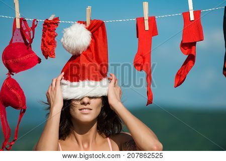 New year girl on sunny blue sky. Christmas woman outdoor. Xmas red costume on rope with pin. Laundry and dry cleaning. Santa claus girl hanging clothes for drying.