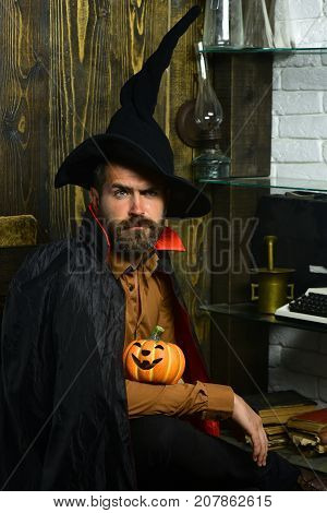 Halloween man in witch hat and cloak. Wizard sitting with pumpkin on wooden wall. Magic and evil spell. Wizardry and witchcraft. Holiday celebration concept.