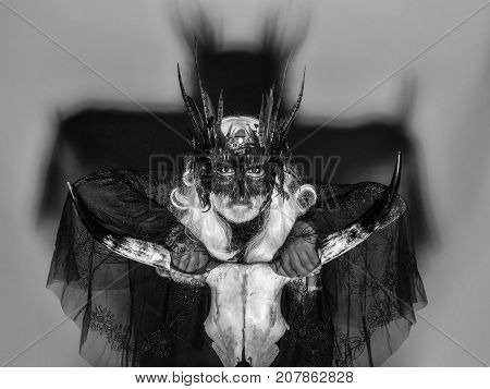 Gothic man in masquerade mask with feathers on his face long white hair and beard in black theater costume on background of big shadow holding cranium of horned animal