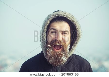 Hipster in coat and hood. Christmas man with long beard. Xmas party celebration. New year guy on blue sky with snow. Winter holiday and vacation.