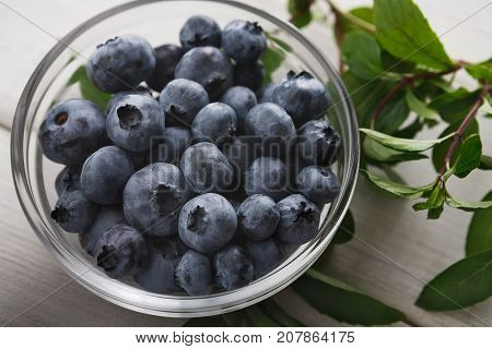 Fresh organic blueberries in glass bowl closeup. Heap of ripe bog whortleberry and mint on rustic wooden table, top view