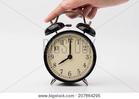 hand lies on the black alarm clock on white background
