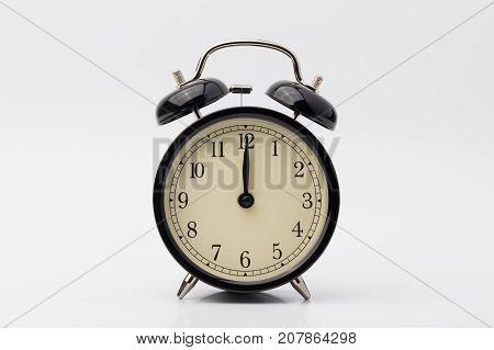 black alarm clock on white background, twelve o'clock