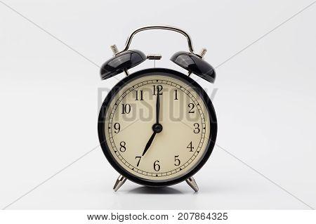 black alarm clock on white background, seven o'clock