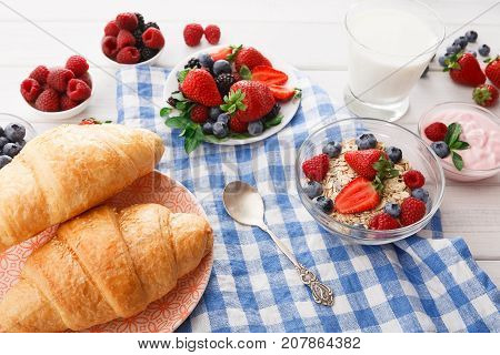 Rich continental breakfast. French crusty croissants, muesli, glass of fresh milk and lots of sweet berries for tasty morning meals. Delicious start of the day