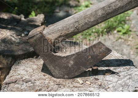 Old used weathered wooden axes stuck on wooden log for splitting wood into farmyard