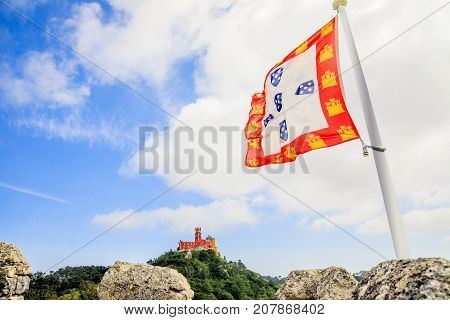 Aerial view of Pena Palace on top of a hill above Sintra an ancient portuguese flag in the foreground. Palacio da Pena is a National Monument, Unesco Heritage and one of Seven Wonders of Portugal.