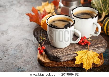Autumn still life with enamel cups with coffee pumpkins and maple leaves