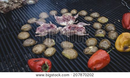 Grilling delicious poultry quails on barbecue. Pepper quail and potato prepared on the grill on sunny day. Culinary concept with delicious food.