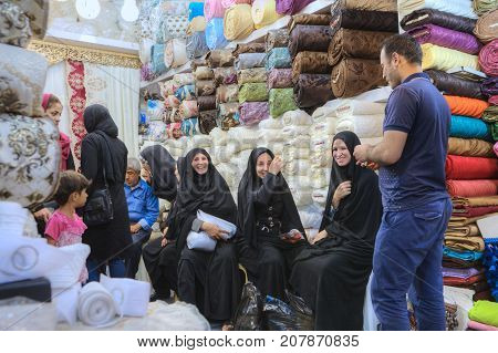 Fars Province Shiraz Iran - 19 april 2017: Several Iranian women in black Muslim clothes rest and laugh in the tissue department of the central market.