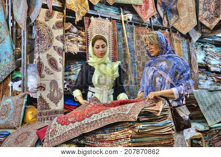 Fars Province Shiraz Iran - 19 april 2017: Two fashionable Iranian women young and mature dressed in bright colorful hijabs choose the goods in a carpet store in the central market.