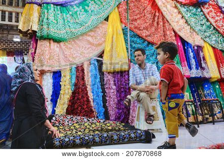 Fars Province Shiraz Iran - 19 april 2017: The department of fabrics in the central bazaar buyers inspect the goods the seller misses sitting on a chair.