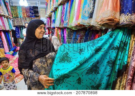 Fars Province Shiraz Iran - 19 april 2017: One unknown elderly Iranian Muslim woman chooses a cloth in the textile shop of the Grand Bazaar.