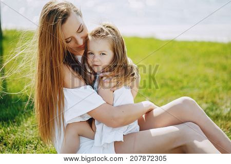 a beautiful young long-haired mom sitting in the park with her beautiful little daughter