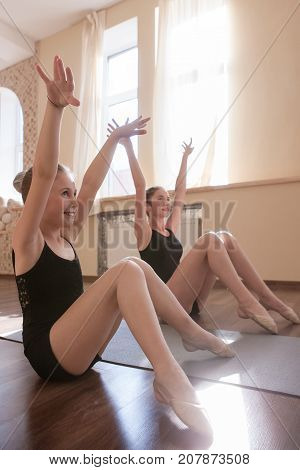 Young ballerinas exercises. Sport for girls. Happy ladies stretching in dance class, sensibility from childhood. Gym background, healthy teen lifestyle, femininity concept