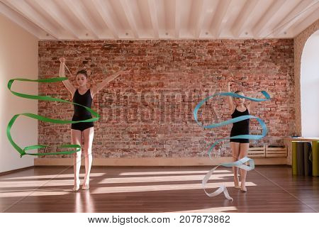 Young ballerinas rehearsal. Rhythmic gymnastics. Teenage sport, healthy teen lifestyle. Pretty girls with flying ribbons, dance class background with free space, ballet concept