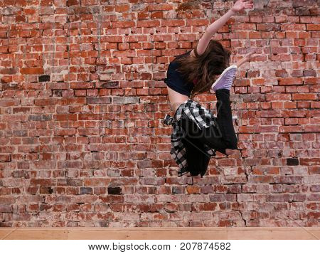 Dance is freedom. Happiness in moving. Lightness in life, sporty teenage girl on brick wall background with free space. Hip hop lifestyle, dancing young female, breakdance concept