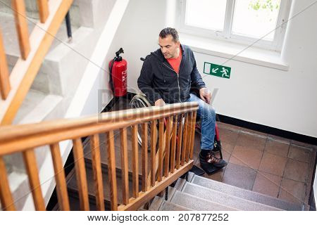 man in wheelchair stuck on the stairs, can go neither up nor down.