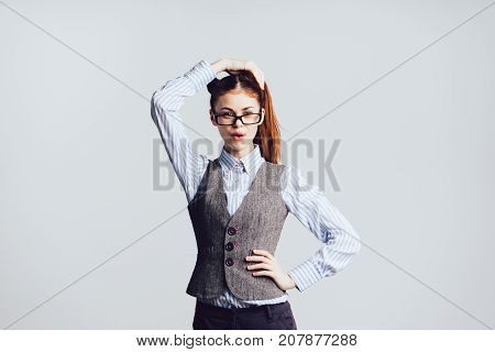 beautiful red-haired girl with glasses, holds her hair and looks directly at the camera