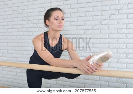 Gorgeous ballerina stretching in ballet class near the ballet barre