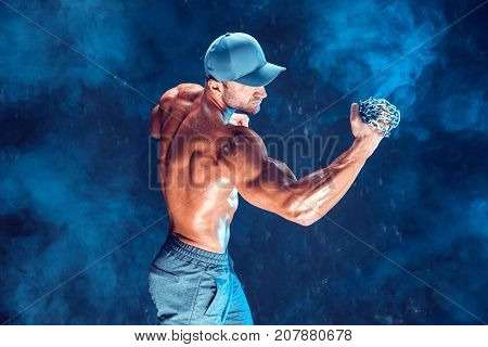 Serious muscular fighter in cap doing the punch with the chains braided over his fist in smoke