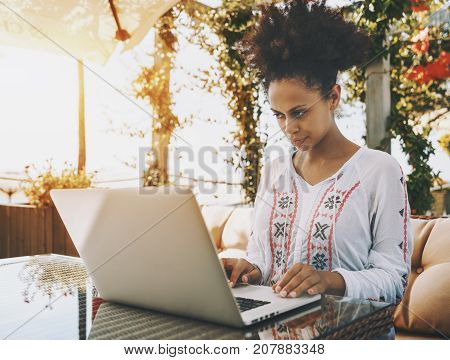 Young black woman in traditional African clothes is working on laptop in cafe outdoors lit by warm sunlight; biracial female with netbook in street bar with plants in background on sunny summer day
