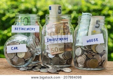 group of glass jar bottles with full of coins and banknotes labeled as investment house car and retirement as savings or investment concept.