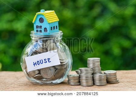 glass jar bottle labeled as house with full of coins and miniature house and stack of coins as home property or mortgage investment concept.