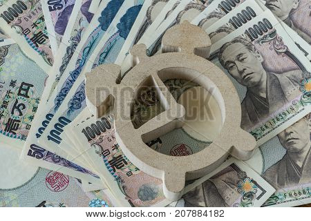 wooden alarm clock on pile of japanese yen banknotes as time count down or deadline financial concept.