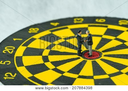 Business goals or agreement concept as miniature people: Small figure businessmen handshaking and standing at the center of dartboard.