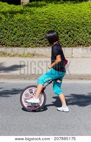 OSAKA JAPAN - SEPTEMBER 18 : unidentified asian little girl starting riding a unicycle (one wheel bike) in a park on September 18 2017 in Osaka Japan.