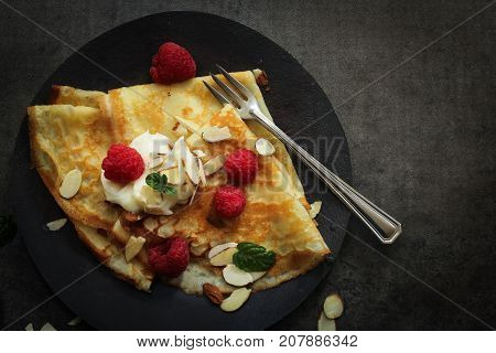 Breakfast Crepes served with Raspberries on dark moody backgroundTop Down view