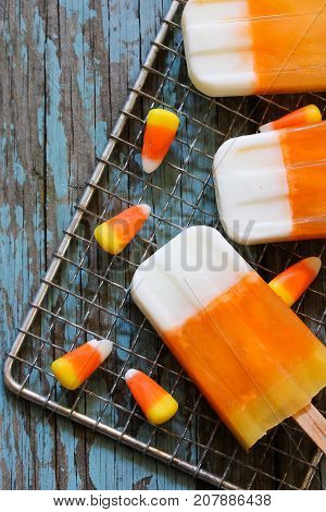 Halloween candy corn Popsicle on wooden background