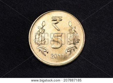 Close up of shiny five Indian Rupee coin on black background.