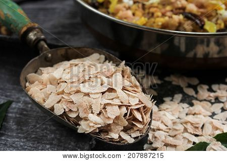Brown Poha or Aval / flattened Rice flakes in a metal scoop selective focus