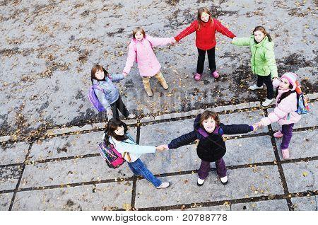 happy school girls running outdoor at sunny autumn day