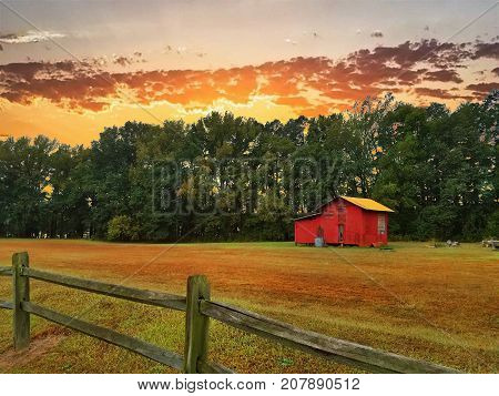 An old red barn on a farm during a beautiful golden sunset.
