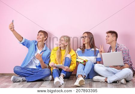 Teenagers taking selfie while sitting on floor near color wall