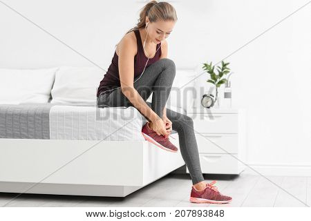 Young sporty woman with phone tying shoelaces at home