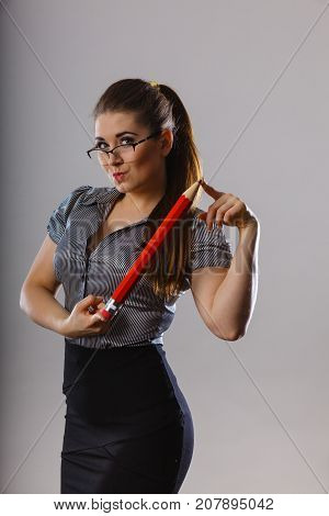 Teacher looking elegant woman wearing dark tight skirt shirt and eyeglasses holding big oversized pencil