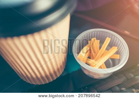 Snack and take away paper hot coffee drinking cup on wooden table with bright sunlight. Vintage film filter effect. Shallow depth of field (dof) snack in focus.