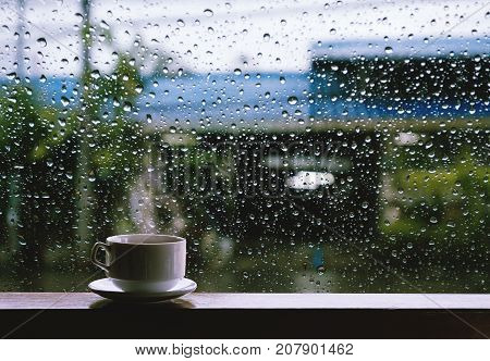 Cup of Hot Drinks on wooden table in rainy day