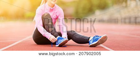panorama of young attractive woman tying shoelaces before or after training enjoying time after good workout sun flare no face visible
