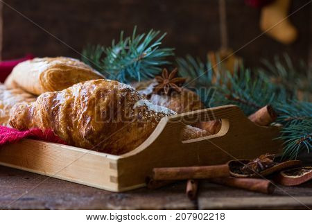 Christmas and New Year 2017 background with continental breakfast - cinnamon fresh orange and croissant. Decorations - snowflake crochet napkin pine cones.
