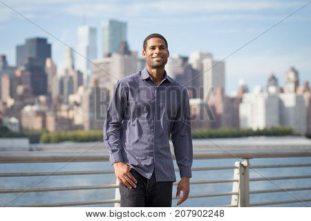 Young handsome African American man smiling and looking optimistic with NYC skyline in the background shot in NYC in September 2017