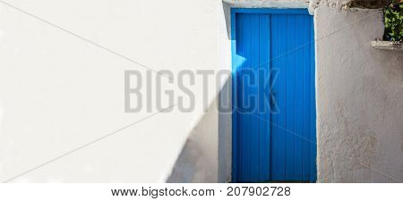 Classic home and architecture on mediterranean islands featuring a blue door and whitewashed walls.